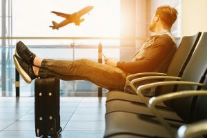Man sitting at airport with feet on luggage