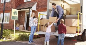 young family taking items out of removals truck