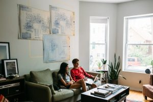 Young couple sitting in living room of apartment