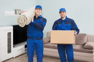 Two men holding box and rug