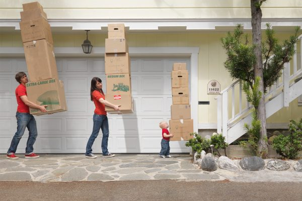 Man woman and baby carrying boxes while walking towards the stairs